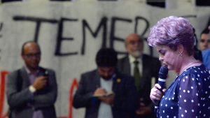 Seinässä teksti Temer, etualalla mikrofoniin puhuva Dilma Rousseff.