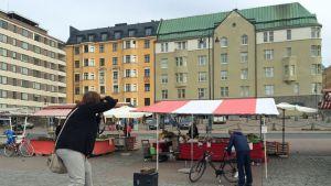 Matkavalokuvaamista harrastava Tuija Kolari seisoo tyhjällä toripöydällä ja ottaa kamerallaan kuvaa.