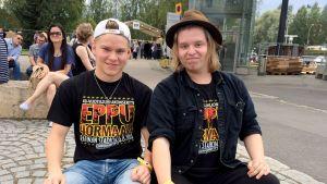 kaksi poikaa istuu kadun varressa