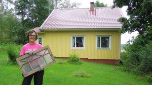 Marika Mattila entisen kesämökkinsä, eli nykyisen kotinsa pihamaalla.