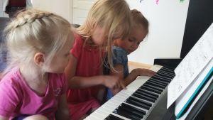 Tenkun lapset pianon ääressä.