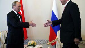 Putin ja Erdoğan lippujen edustalla kädet ojossa hetki ennen kättelyä.