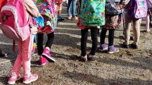 Pieniä koululaisia isot värikkäät reput selässään.