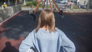 Tyttö katsoo, kun toiset lapset leikkivät koulun pihalla.