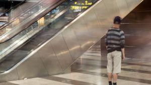Anonyymi ihminen seisoo paikallaan ostoskeskuksessa.