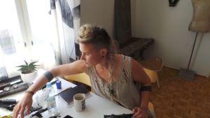Jenni Ahtiainen tekee työtä pöydän ääressä.