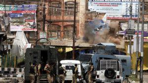 Rakennuksesta nousee savua. Intian turvallisuusjoukkojen miehiä seisoo panssaroitujen ajoneuvojen ja jeeppien takana.