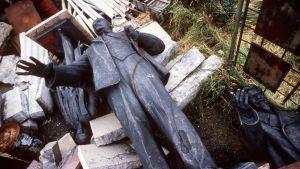 Tuhottu Leninin patsas makaa maassa roskien seassa.