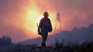 Etualalla palomies, taustalla liekehtivä taivaanranta ja sähkölinjoja.