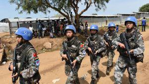 YK:n kiinalaisia rauhanturvaajia kävelemässä kadulla.