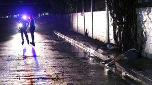 Poliiseja epäiltyjen huumekauppiaiden ruumiden vierellä Manilassa.