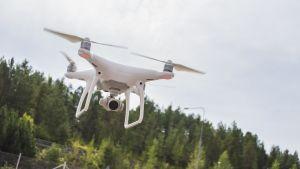Valkoinen minikopteri leijuu ilmassa. Kopterin pohjassa on kamera.