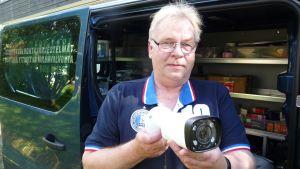 Turva-alan yrittäjä Hannu Heinonen ja valvontakamera.
