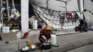 Tyttö pesee astioita rakennuksen katokseen väsätyn teltan edessä.