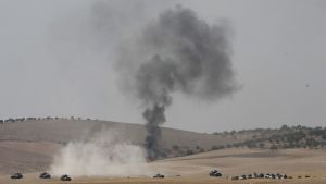 Pellon keskellä näkyy ammuksen aiheuttama savupatsas, ympärillä panssarivaunuja.