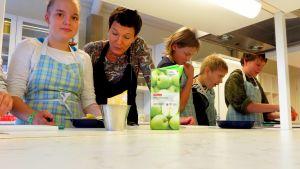 Lehtori Heli Kukkohovi opastaa 7-luokkalaisia veitsien käytössä.