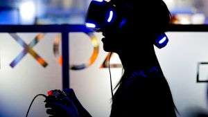 Henkilö virtuaalilasit päässään ja konsoliohjain käsissään.