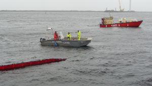 Pelastuslaitoksen vene ja Kemin sataman alus Ahti vetämässä öljyntorjuntapuomia Ajoksen satamassa.