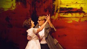 Näyttelijät Teija Auvinen ja Ilkka Heiskanen tanssivat hehkuvan punakeltaisen lavasteen edessä.
