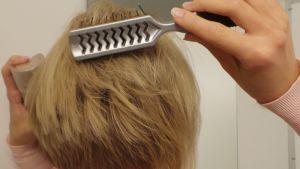 nainen/tyttö laittaa hiuksiaan