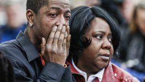 Kaksi surevaa ihmistä. Mies kyyneleet silmissä pitää käsiään suun edessä.