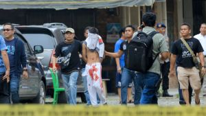 Kaksi poliisia taluttaa hoikkaa miestä, jonka kasvot on peitetty paidalla. Miehellä on housuissaan punaisia läikkiä, jotka näyttävät vereltä.