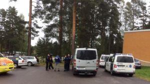 Piiritystilanne Iitin Kausalassa 30. elokuuta 2016. Poliiseja ja poliisiajoneuvoja Iitin terveysaseman pihalla.