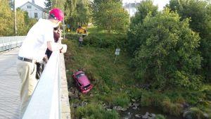 Punaista autoa nostetaan joesta.