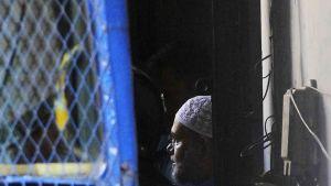2. marraskuuta 2014 päivätyssä kuvassa bangladeshiläistä islamistijohtajaa Mir Quasem Alia siirretään viranomaisten huomaan oikeusistuntonsa päätyttyä Dhakassa, Bagladeshissä.