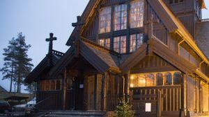 Puinen kirkkorakennus talvihämärässä.