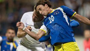 Paulus Arajuuri kamppailee pallosta Kosovon Hekuran Kryeziuta vastaan.