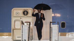 Sateenvarjoa pitelevä mies astuu ulos lentokoneesta vilkutten.