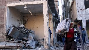 Nainen kantaa patjaa ja kokoon taitettua vuoteen metallirunkoa talon rauniosta.