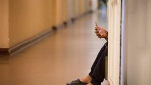 Kuvassa näkyy kännykkää näppäilevä turvapaikanhakijan käsi vastaanottokeskuksessa Saksan Wilmersdorfissa.