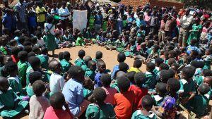 Lapsia istuu ja seisoo piirissä kuuntelemassa opettajaa.