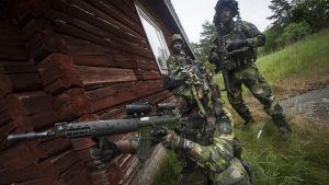 Yksi sotilas polvillaan talonkulmalla, kaksi hänen takanaan. Sotilailla maastopuvut päällä.