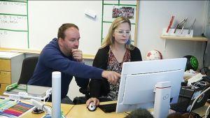 Kaksi henkilöä tietokoneella.