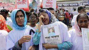 Itkevät naiset kantavat tehtaan romahduksessa kuolleiden kuvia.