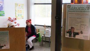 Geronomiopiskelija Kati Huttunen palvelemassa asiakasta