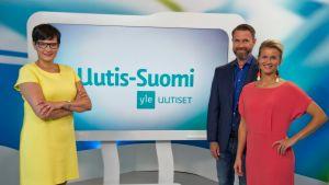 Uutis-Suomen juontajat Salla Paajanen, Mikko Hirvonen ja Milla Madetoja seisovat ohjelman lavasteissa.