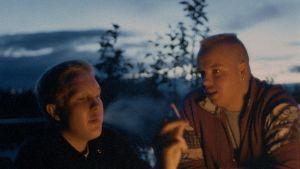 Dokumentissa kaksi nuorta miestä viettää aikaa hämärässä luonnossa.