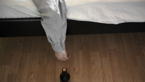 Olut pullo sängyn vieressä lattialla.