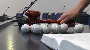 Golfpallot pöydällä ja lakikirja.