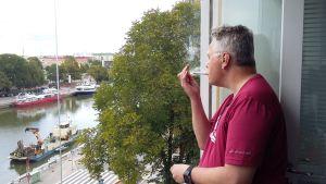 Mies tupakalla parvekkeella.