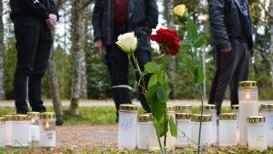 Kynttilöitä ja kukkia surmapaikalla.