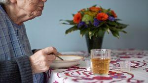 Vanhus syö pöydän ääressä.
