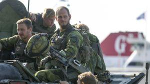 Kaksi ruotsalaista sotilasta istuu panssarivaunun päällä maastopuvuissa. Kolmas on maassa ja pitää kädellä kiinni vaunusta.