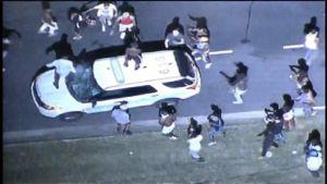 Helikopterista otettu kuva, jossa joukko mielenosoittajia hyökkää poliisiauton kimppuun. Yksi mielenosoittaja seisoo auton katolla ja toinen seisoo konepelillä ja potkii auton etuikkunaa.
