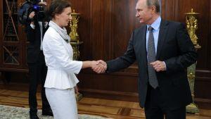 Anna Kuznetsova ja Vladimir Putin kättelevät Putinin työhuoneessa, jonka seinät ovat tummaa puupaneelia. Molemmat hymyilevät. Kuznetsovalla on valkoinen asu, Putinilla tumma puku, vaaleansininen kauluspaita ja kravatti. Taustalla kirjahyllyn edessä näkyy television kameramies, joka kuvaa tilannetta.