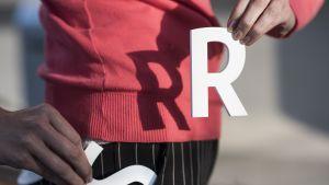 Nainen pitelee kädessään R-kirjainta ja työntää taskuun S-kirjainta.